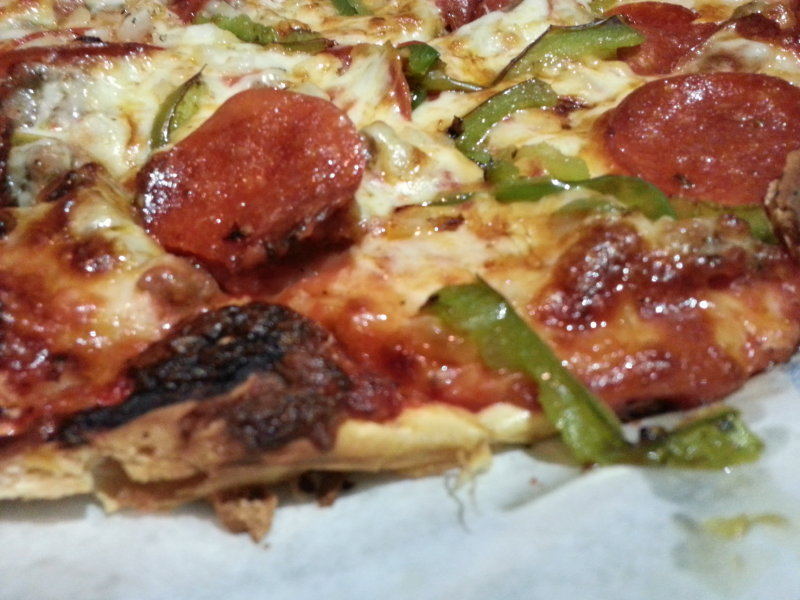 The thin-crust pizza with sausage, pepperoni, green peppers and onions.