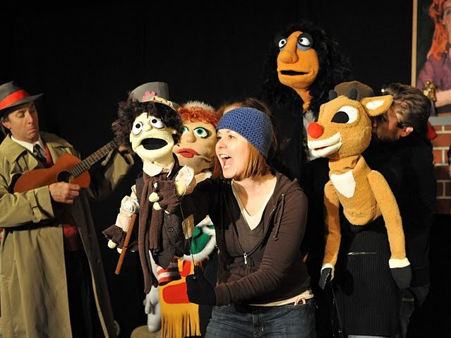 """Bo Johnson and Amy Geyser onstage with the puppets of """"Who Killed Santa?"""""""