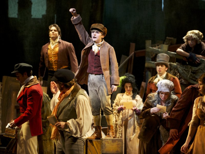 "Young Gavroche (Luke Brotherhood) cheers on a revolution in ""Les Miserables."""