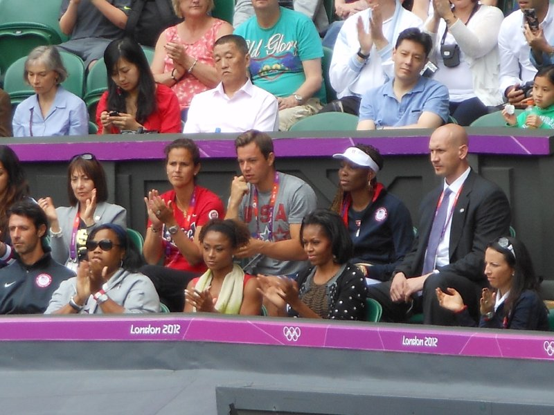 First Lady Michelle Obama and Venus Williams watch Serena on the court.