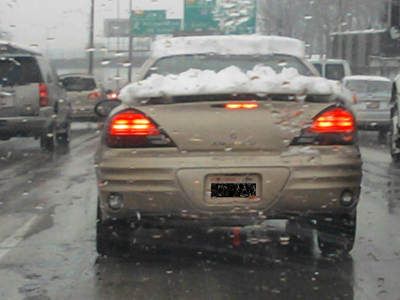 The elusive super marshmallow: a car with snow on the roof and trunk.