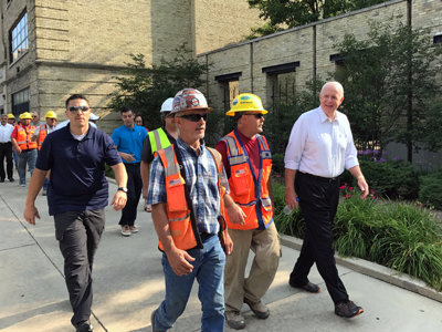 Mayor walks streetcar route section with workers who are building it