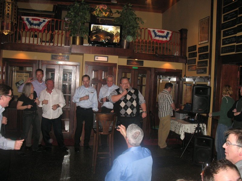 "A group of Canadian businessmen sing ""Sweet Caroline"" at the Newsroom Pub."