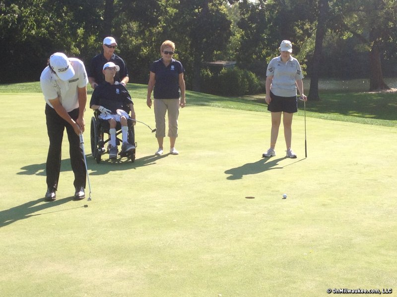 2013 PGA Champion Jason Dufner sinks a putt as his special needs playing partners look on.