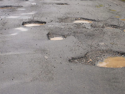 Mayor pitches in to fill potholes Image