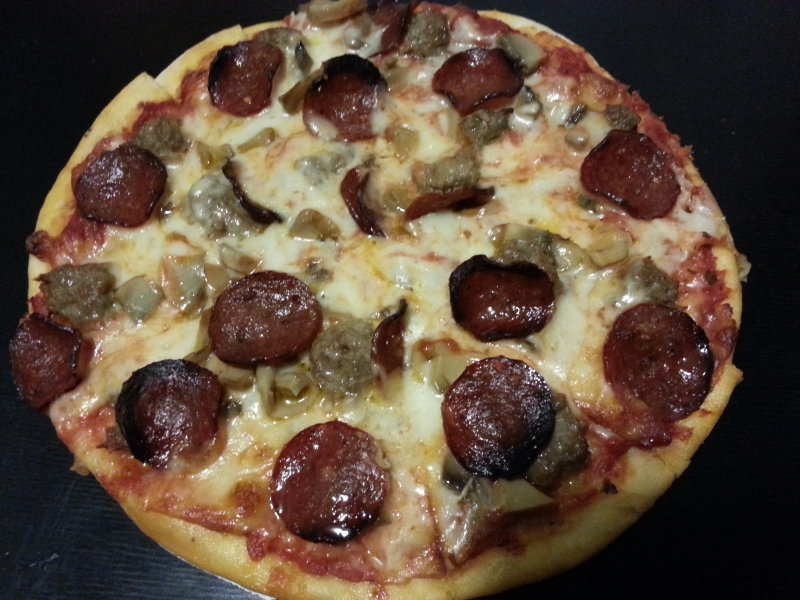 Sausage, pepperoni and mushrooms on thin crust pizza.