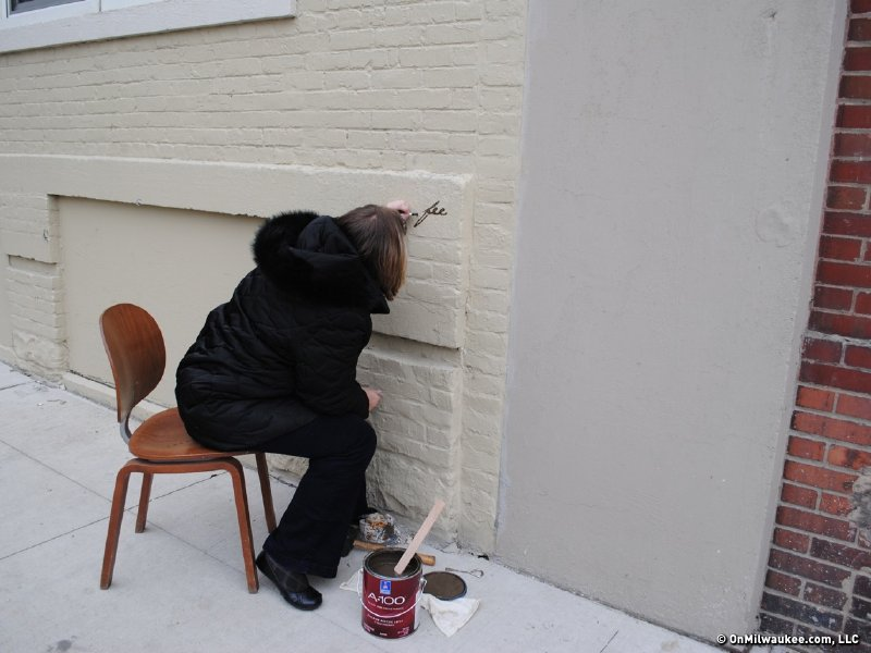 An artist hand paints final details on the building.