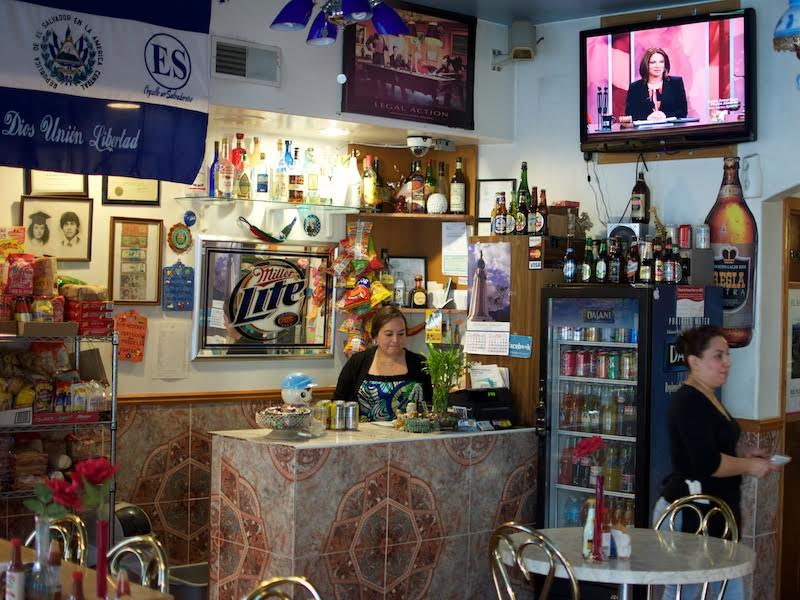 The Walls Are Adorned With Salvadoran Art Flags Tiles And A Of Flatscreen Televisions Playing Spanish Language Programs