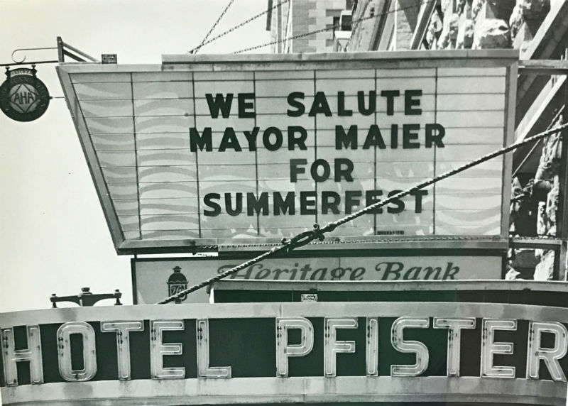 "A vintage sign above the Hotel Pfister reads ""We salute Mayor Maier for Summrfest"""