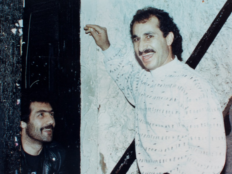 A photo from the '80's shows Gus Housseni in the corner in a black leather jacket, met by a mustachioed man leaning against the wall in a patterned white pullover.