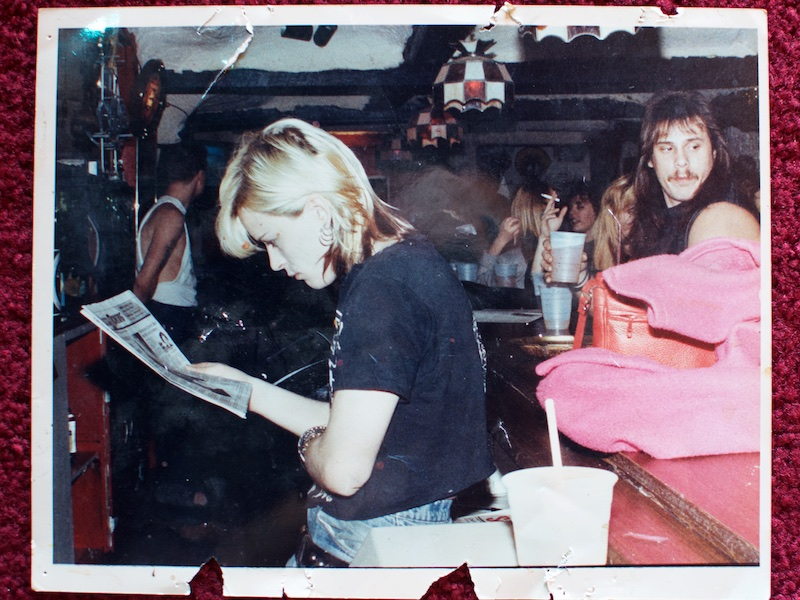 A young woman with dyed blonde hair and a black t-shirt stands behind the bar, leaning against the bar, turned away from the patrons, reading the front page of a newspaper.