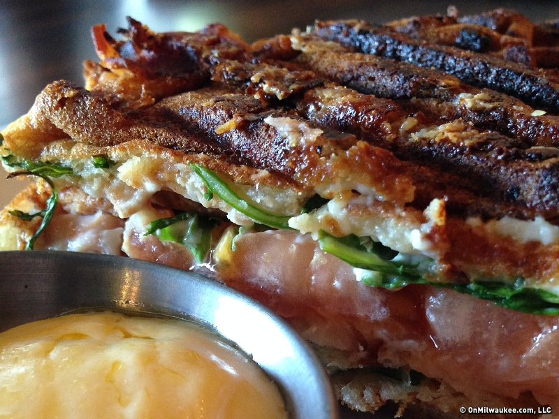A waffle panino: smoked salmon with horseradish cream cheese, arugula, bacon and a side of hollandaise.