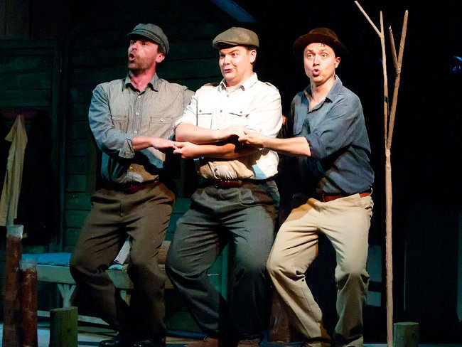 "From left, Steve Koehler, Dan Klarer and Chad Luberger kick up their heels in the American Folklore Theatre production of ""Victory Farm."""